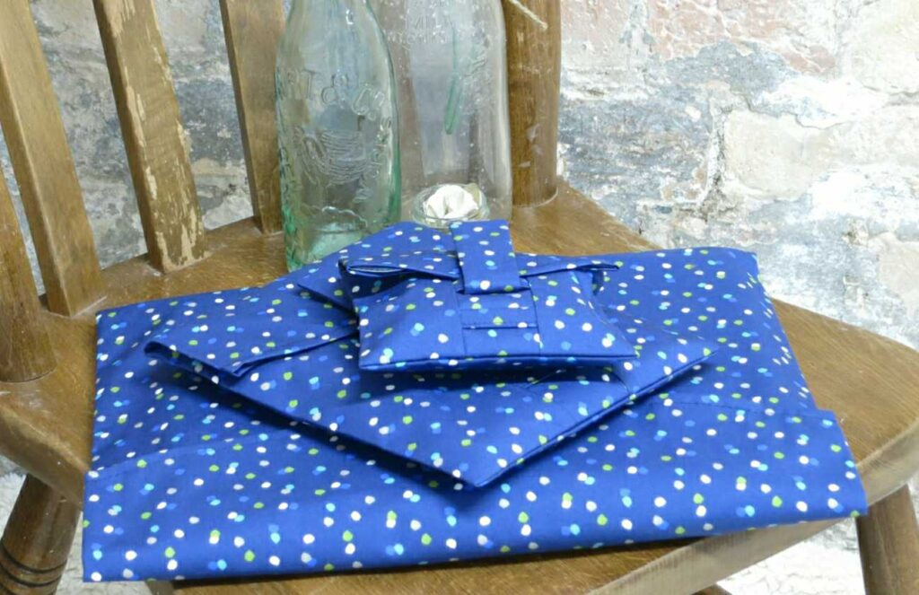 A pile of gifts in reusable navy wrapping paper; fabric wrap that can be torn open by their velcro strap