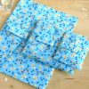 A pile of Blue Butterfly sustainable wrapping paper, made from organic cotton, that can be torn open by the Velcro tab