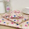 A pile of reusable fabric wrap in a peach floral fabric; fabric wrap that can be torn open by their velcro strap