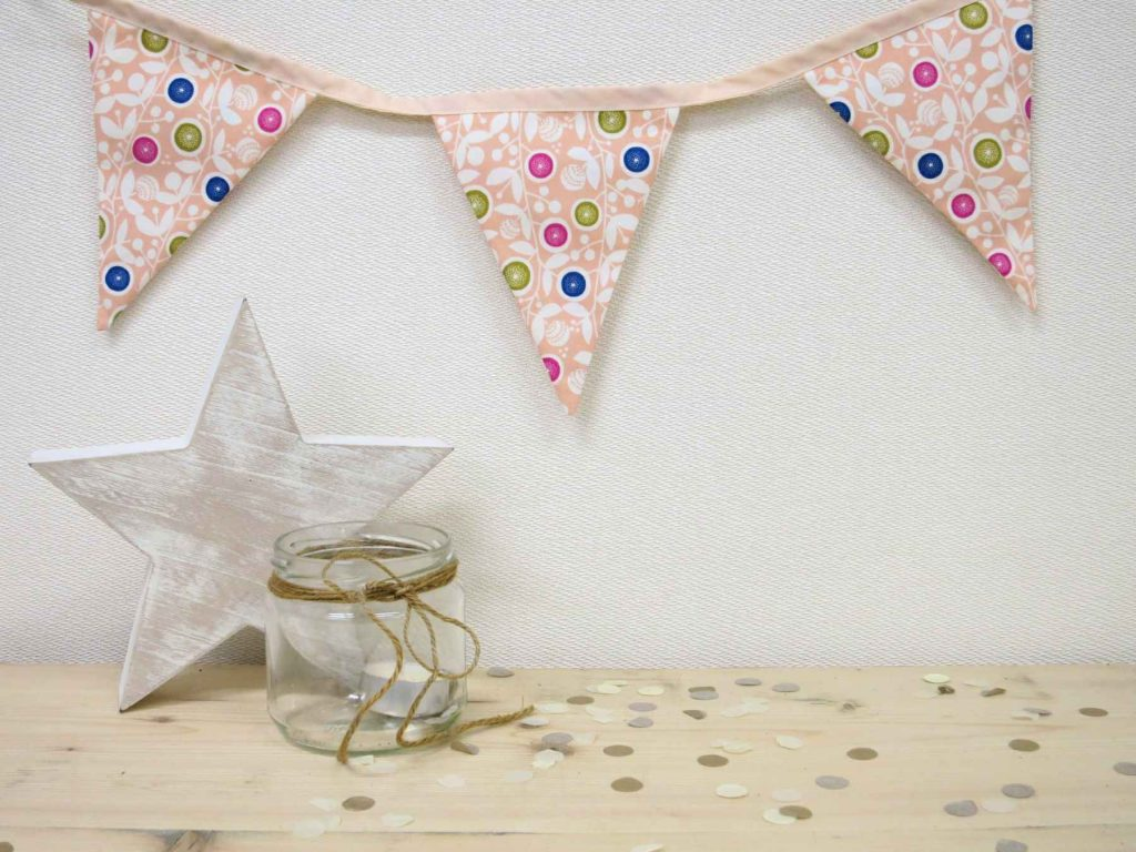 A string of pale-peach floral bunting hanging on a wall