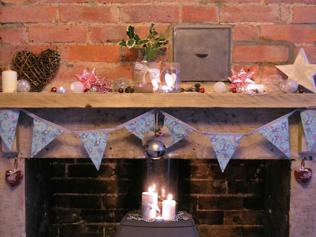 Christmas reindeer bunting hanging on a fireplace, with candles and festive decorations