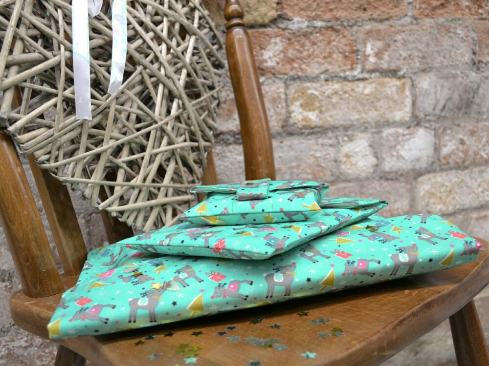 A pile gifts in Reindeer wrapping paper, that can be torn open by their Velcro strap