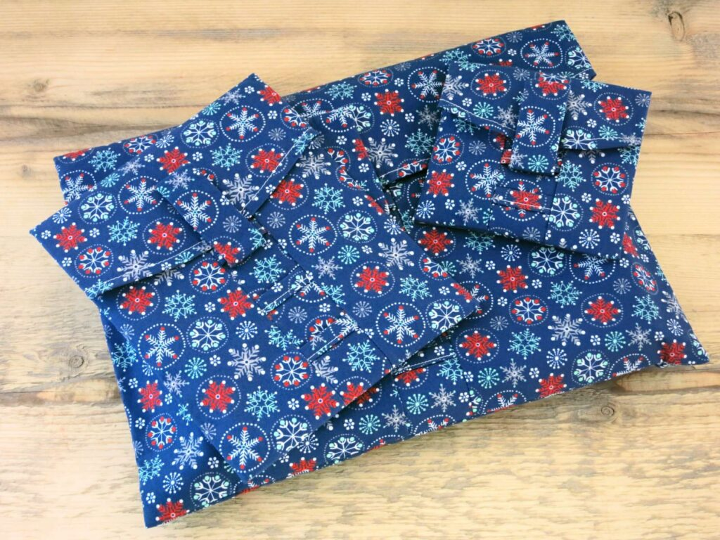 A pile of reusable navy Christmas wrapping paper; fabric wrap that can be torn open by the velcro strap
