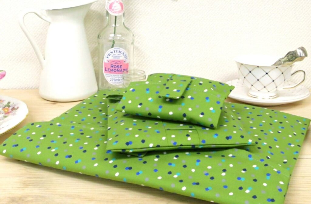 A pile of reusable green wrapping paper; fabric wrap that can be torn open & reused