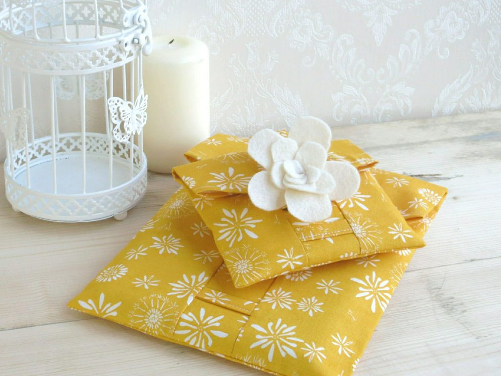 Pile of gold eco wraps made from organic cotton; that can be torn open by the Velcro tab
