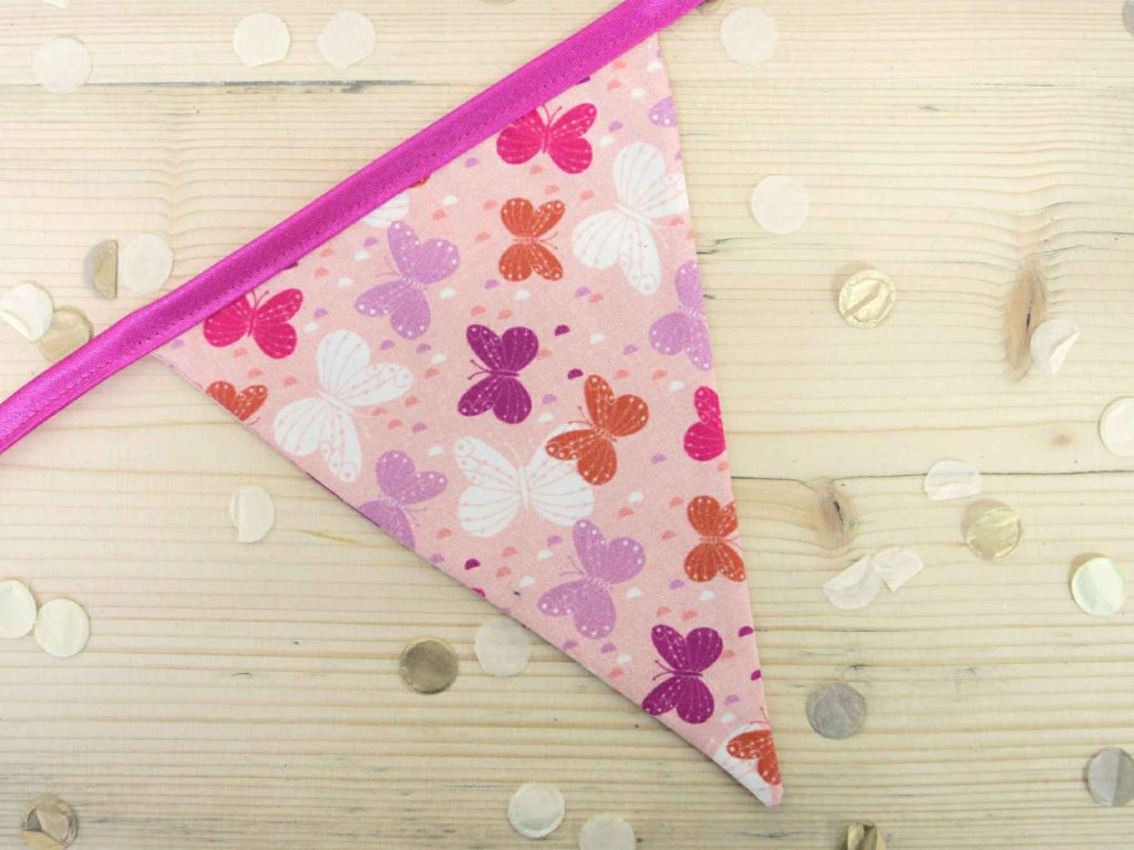 A single flag of pink bunting; made with pink butterfly fabric and a pink ribbon