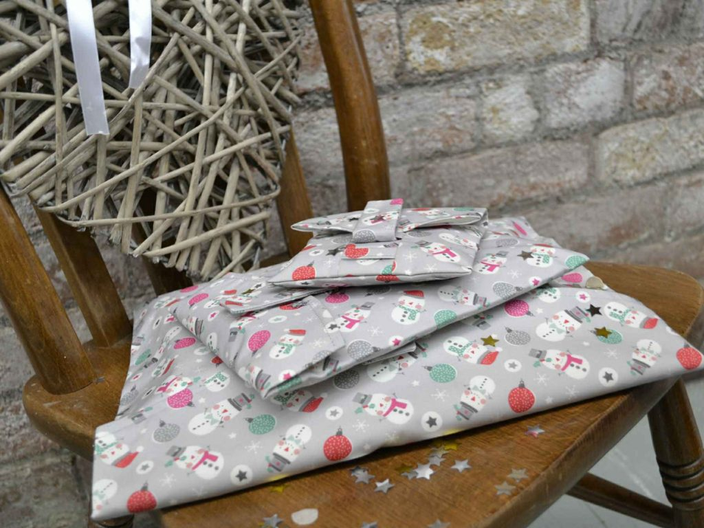 A pile gifts in Snowman wrapping paper, that can be torn open by their velcro strap
