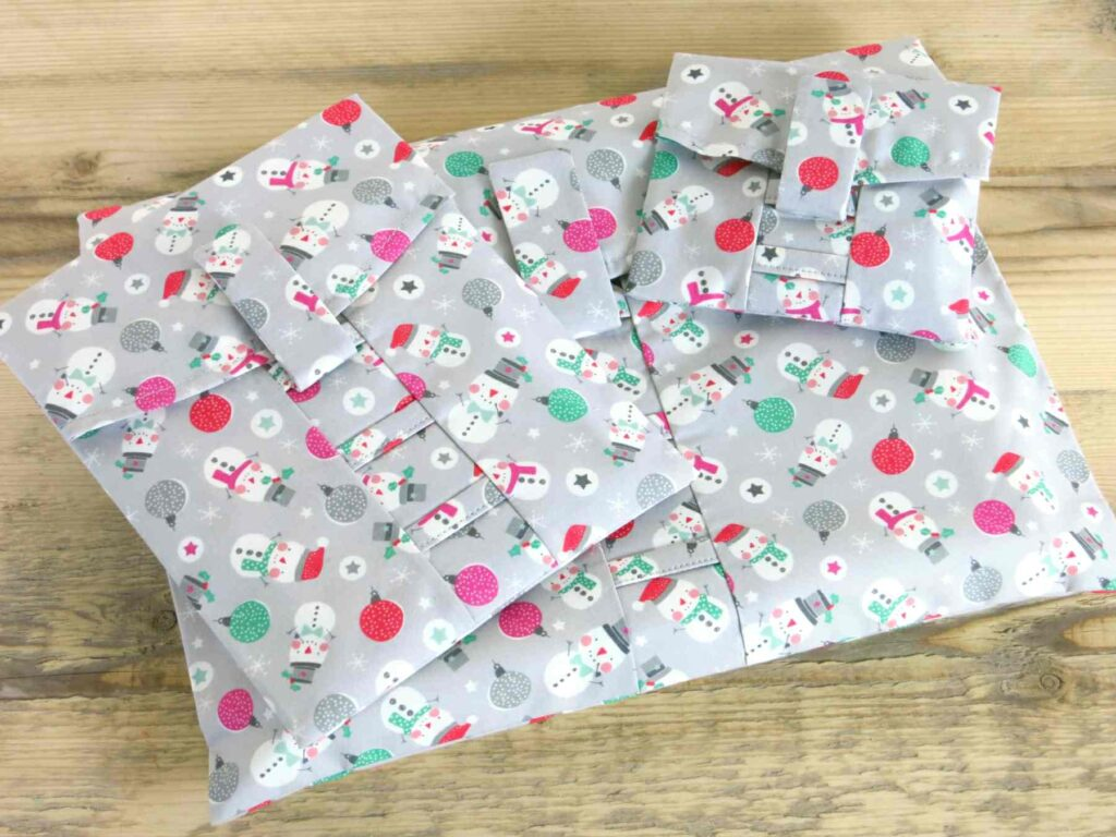 A pile gifts in Snowman wrapping paper; fabric wrap that can be torn open by their velcro strap