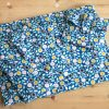 Pile of blue floral gift wrap bags, made from organic cotton, that can be torn open by the Velcro tab