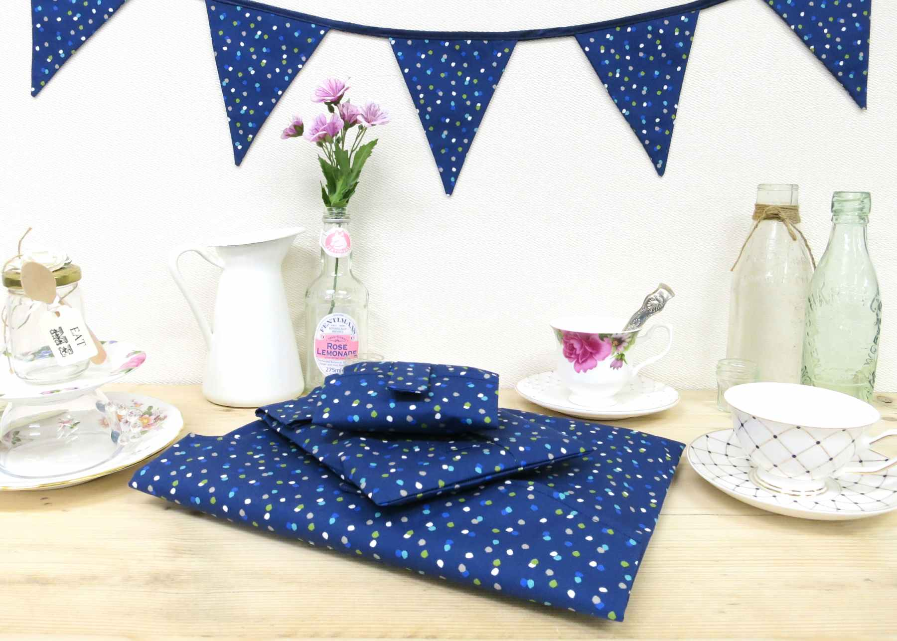 A setting for birthday tea, with Blue Spotty bunting and reusable gift wrap