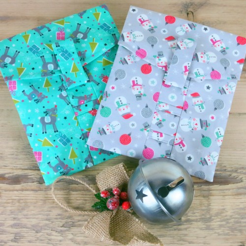 Two Christmas reusable gift wrap pouches with a bauble; one Reindeer and one Snowman