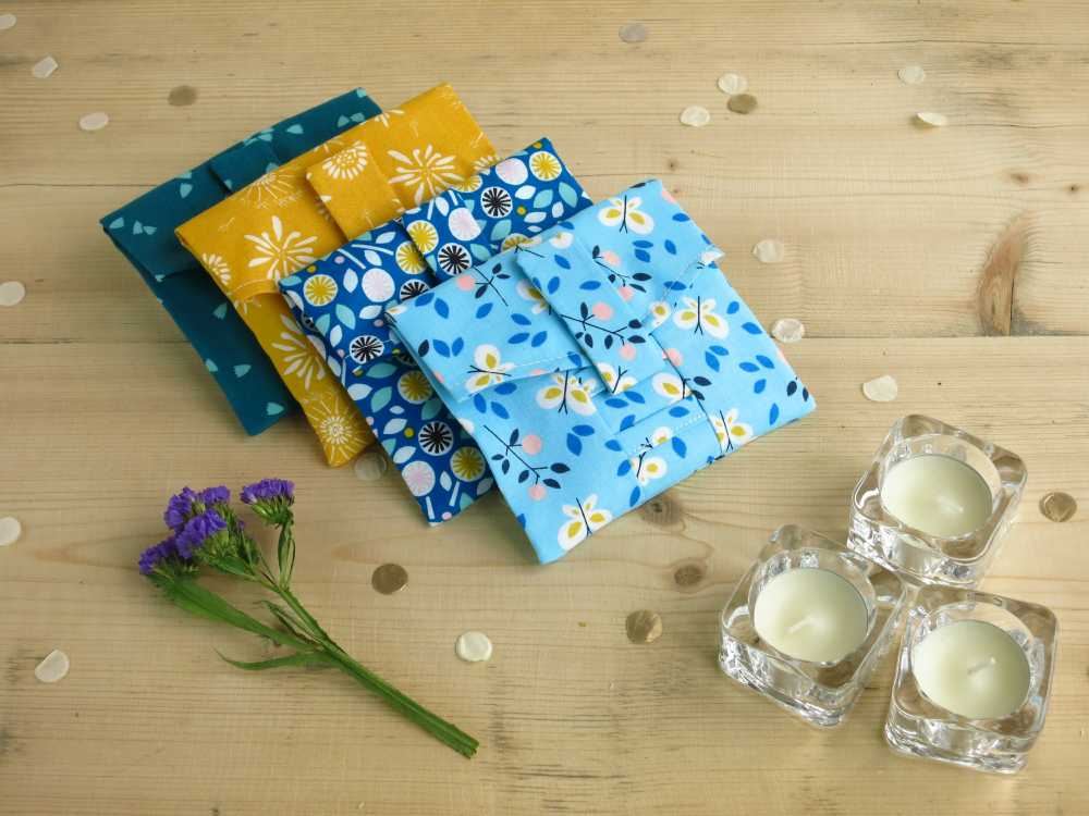 Reusable gift wrap in four different fabrics arranged with candles and dried flowers