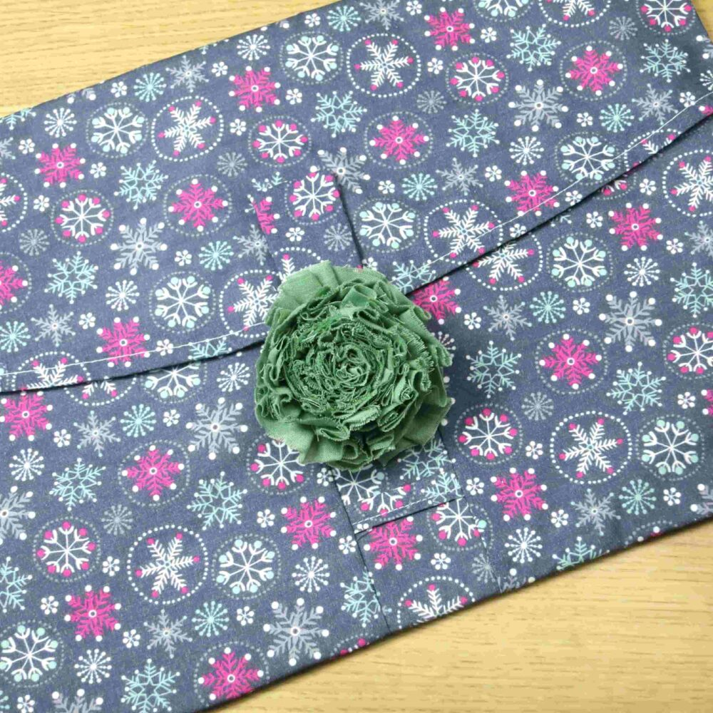 Large green fabric flower on a large gift wrap