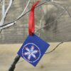 A navy snowflake gift tag tied with a red ribbon