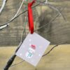 A Snowman gift tag hanging from a branch
